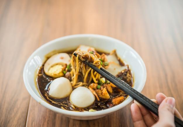 Hand met chinese eetstokjes die noodle eten, een beroemde maleisië loh mee.