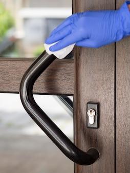 Hand met chirurgische handschoen desinfecterende deurklink