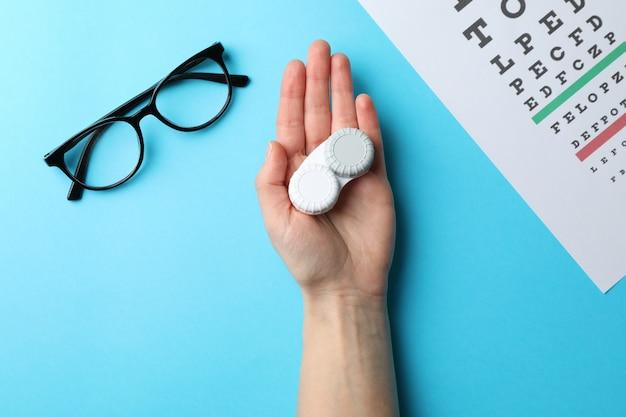 Hand met contactlenzen, bril en oog test-chart op blauw oppervlak, bovenaanzicht
