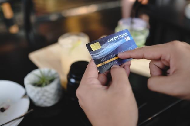 Hand met creditcard in café.