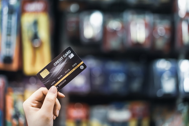 Hand met creditcard met vervagen supermarkt, winkelen en detailhandel concep