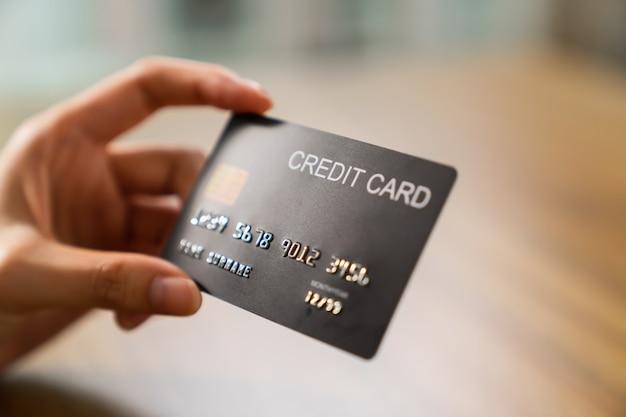 Hand met creditcard op houten tafel.