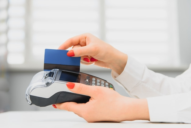 Hand met creditcard veeg door terminal te koop in supermarkt
