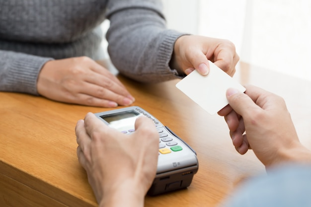 Hand met creditcard veeg door terminal voor betaling