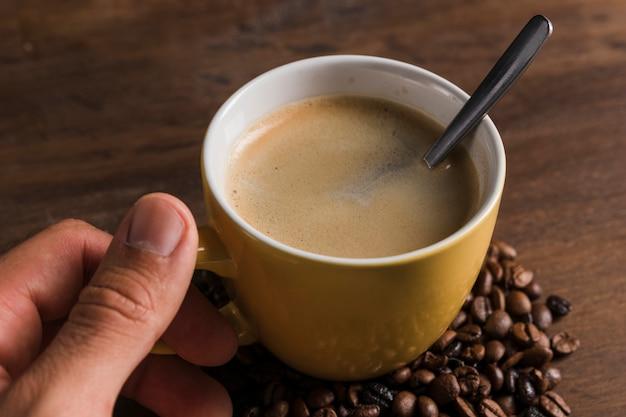 Hand met cup met lepel en koffie