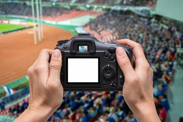 Hand met de camera over abstract wazig foto menigte van toeschouwers op een stadion