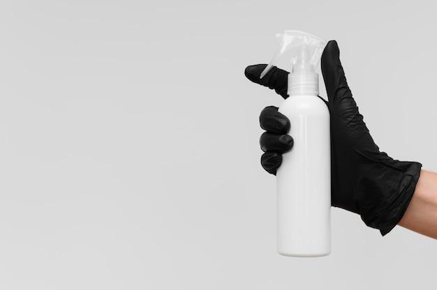 Hand met de fles van de handschoenholding reinigingsoplossing met exemplaarruimte