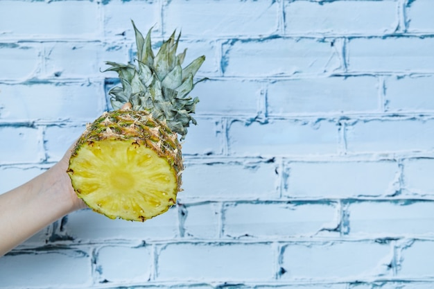 Hand met de helft van ananas op blauwe achtergrond