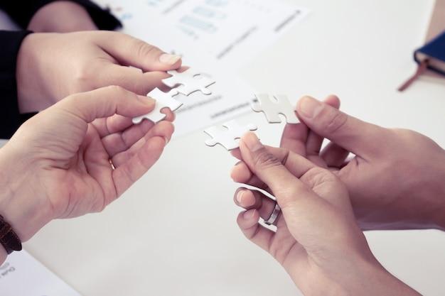 Hand met de puzzels voor de zakenlieden om als team samen te werken. concept van het plannen van werk als teamwerk.