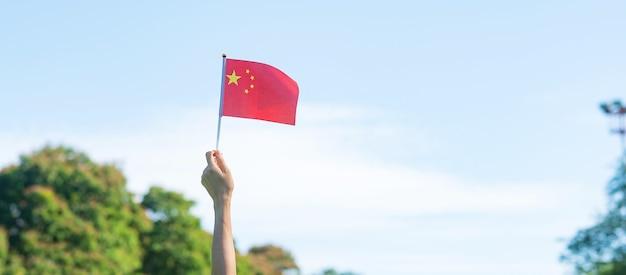 Hand met de vlag van china op blauwe hemelachtergrond. nationale dag van de volksrepubliek china, nationale feestdag en gelukkige vieringsconcepten