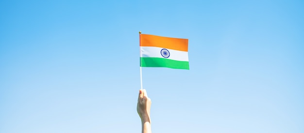 Hand met de vlag van india op blauwe hemelachtergrond. holiday of india republic day, happy independence day en gandhi jayanti-concepten