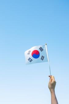 Hand met de vlag van korea op de achtergrond van de natuur. nationale stichting, gaecheonjeol, nationale feestdag, nationale bevrijdingsdag van korea en gelukkige vieringsconcepten