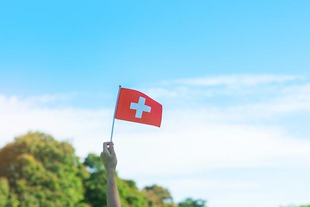 Hand met de vlag van zwitserland op blauwe hemelachtergrond. nationale feestdag van zwitserland en gelukkige vieringsconcepten