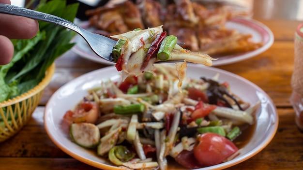 Hand met de vork voor eten papaja salade
