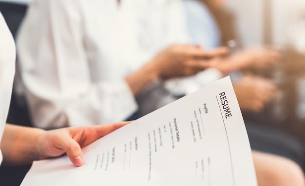 Hand met document en cv indienen bij werkgever om sollicitatie te beoordelen