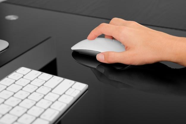 Hand met draadloze muis op zwarte tafel