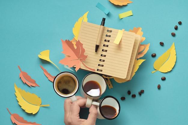 Hand met drie kopjes koffie en notitieblok openen met herfstbladeren gemaakt van papier.