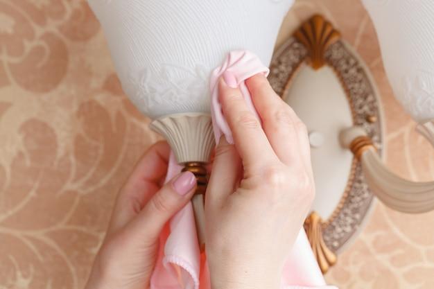 Hand met droge microvezeldoek die een kroonluchter in de ruimte schoonmaakt. vroege voorjaarsschoonmaak of regelmatig opruimen. maid maakt huis schoon.