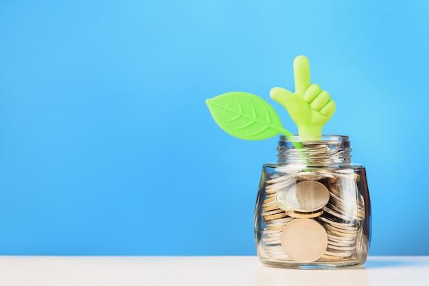Hand met duim omhoog en blad op glazen pot met munten. investeringsgroei concept.