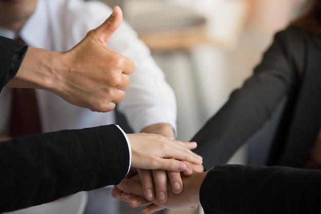 Hand met duim omhoog en stapelen handen in teamwerk.