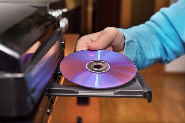 Hand met dvd-invoeging naar videospeler