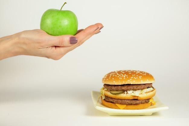 Hand met een appel en een hamburger