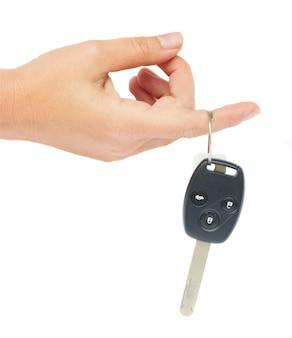 Hand met een autosleutel geïsoleerd