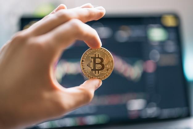 Hand met een bitcoin met grafieken op de achtergrond
