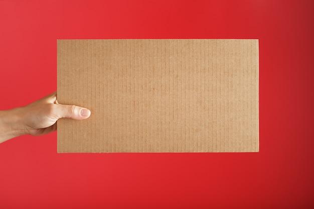 Hand met een blanco vel karton op een rood oppervlak