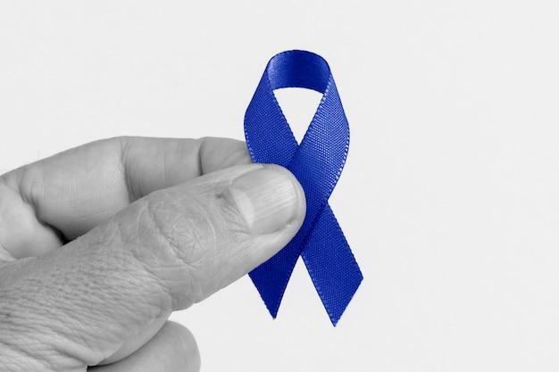 Hand met een blauw lint, colorectale kanker, prostaatkanker bewustzijn, gezondheid voor mannen bewustzijn.