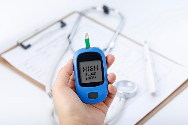Hand met een bloedglucosemeter met bloedglucose, de achtergrond is een stethoscoop en een grafisch bestand