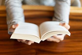 Hand met een boek thuis