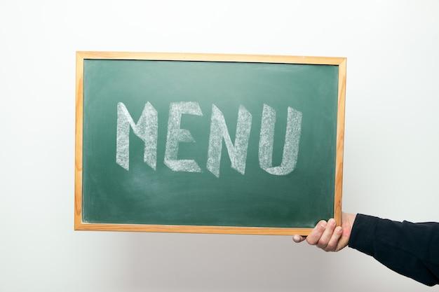 Hand met een bord met het woord menu handgeschreven in krijt