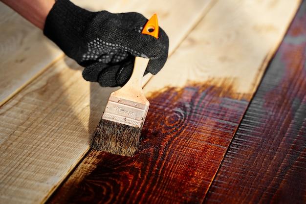 Hand met een borstel die vernisverf op een houten oppervlak aanbrengt