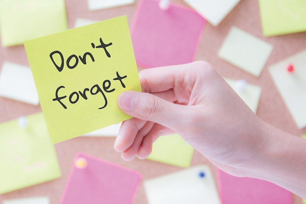 Hand met een briefpapier of post het met woorden niet vergeten