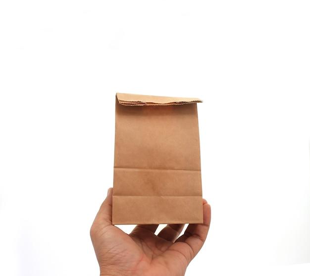 Hand met een bruine papieren zak