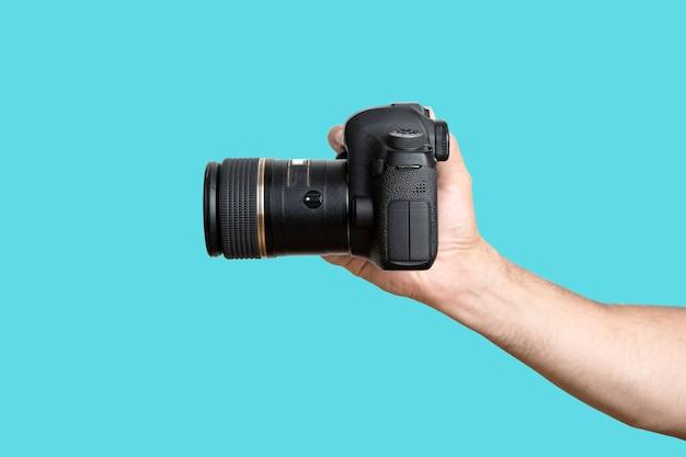 Hand met een camera een hand met een digitale slr-camera op een schone blauwe achtergrond van hoge kwaliteit foto