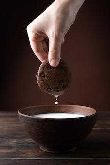 Hand met een chocoladeschilferkoekje waarvan melk druipt