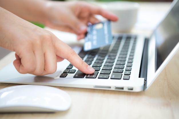 Hand met een creditcard en een laptop