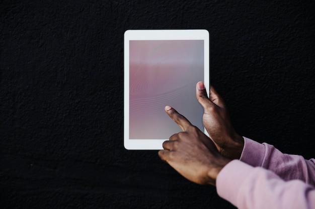 Hand met een digitale tablet op zwarte achtergrond