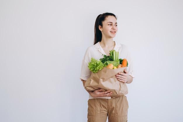 Hand met een eco papieren zak met groenten. jonge hipster levensstijl meisje met papieren zak met groenten. winkelen zonder voedselverspilling. eco natuurlijk concept