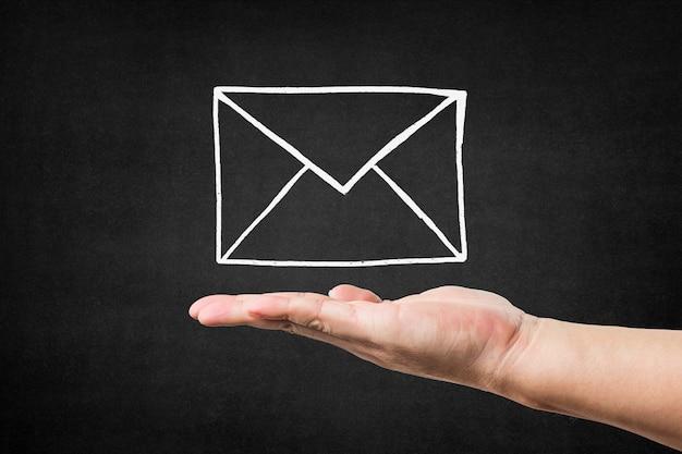 Hand met een envelop op de top getekend op een schoolbord