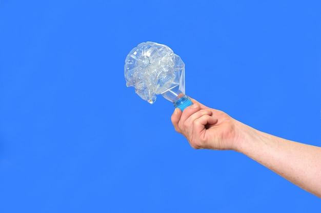 Hand met een fles water om op blauw te recyclen