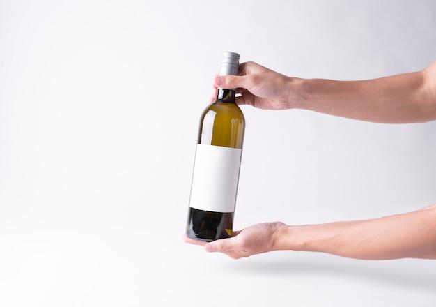 Hand met een fles wijn voor mock-up. leeg etiket op een grijze achtergrond.