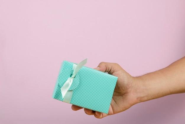 Hand met een geschenkdoos die aan iemand wordt afgeleverd.