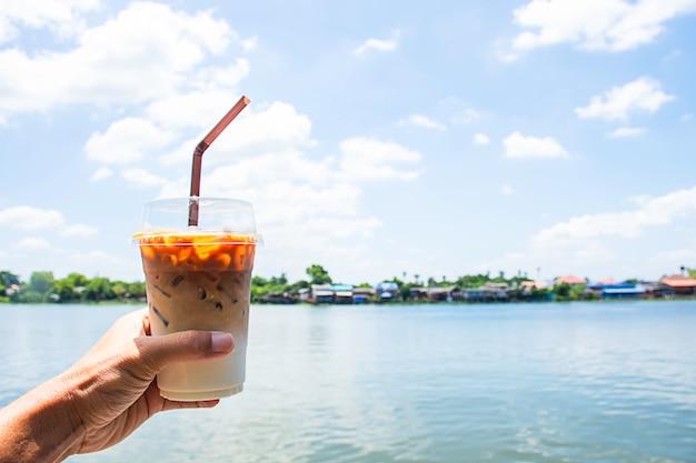 Hand met een glas koude espresso koffie met uitzicht op de rivier en het huis.