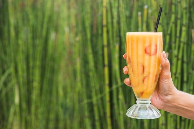 Hand met een glas smoothie in de buurt van bamboe