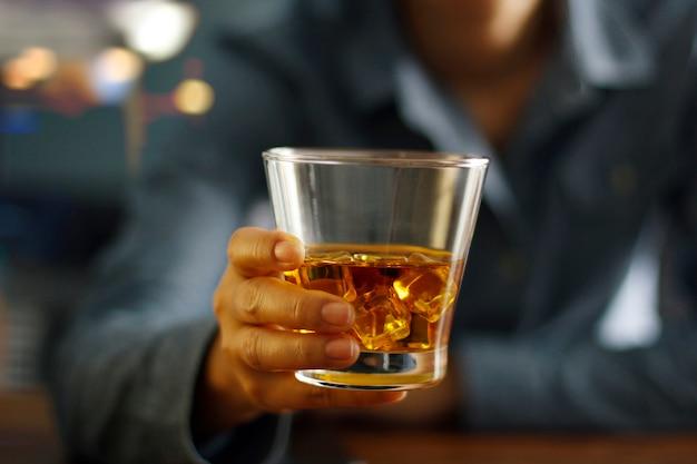 Hand met een glas whisky