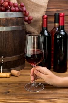 Hand met een glas wijn met flessen en barre