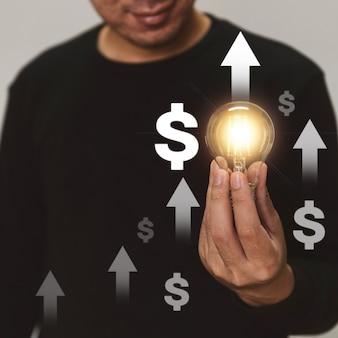 Hand met een gloeilamp stijgt op met investeringspijl voor bedrijfsgroei